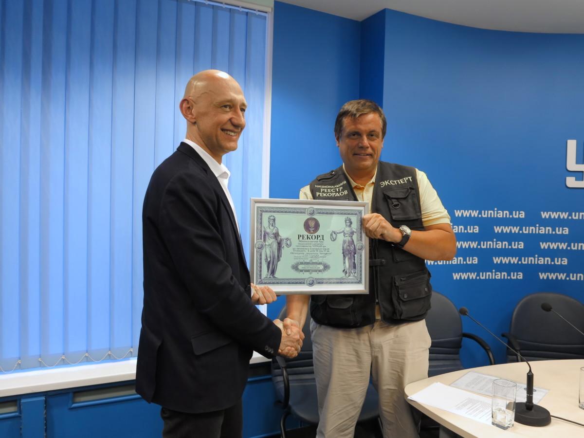Виталий Зорин, руководитель Национального Реестра рекордов Украины вручает почетный диплом Виталию Новаку, заместителю директора Медиагруппы «Автоцентр», организатору автопробега.